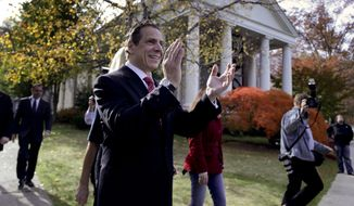 New York Gov. Andrew Cuomo claps his hands to the rhythm of slogans shouted by supporters and demonstrators after casting his ballot, Tuesday, Nov. 4, 2014, in Mount Kisco, N.Y.   A victory by Cuomo over Republican challenger Rob Astorino on Tuesday would make him the first Democratic governor since his father, Mario Cuomo, to win re-election in the nation's third-largest state. (AP Photo/Julie Jacobson)
