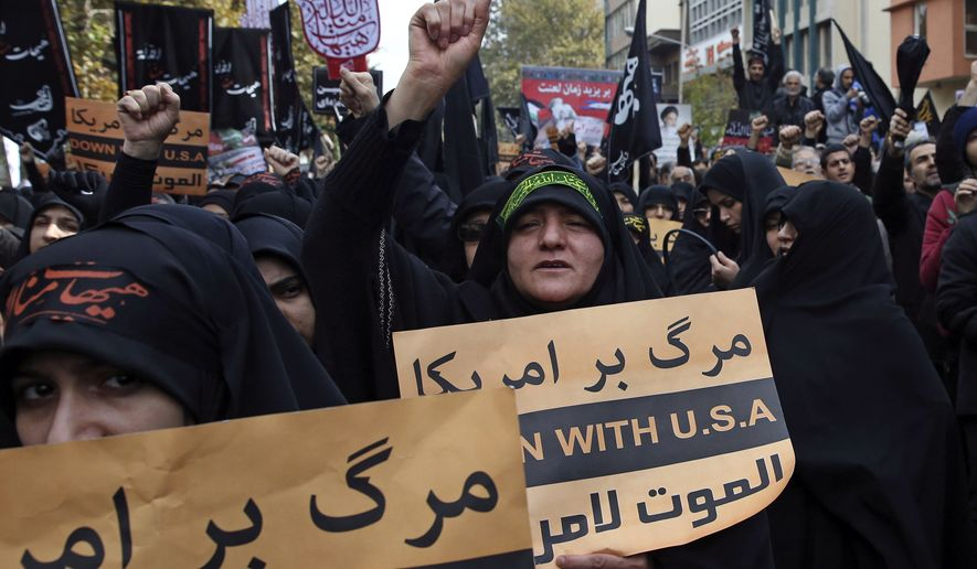 Iranian women chant slogans while holding anti-U.S. placards during a demonstration in front of the former U.S. Embassy, during Ashoura, when Muslim Shiites mark the death of 7th century Imam Hussein, in Tehran, Iran, Tuesday, Nov. 4, 2014. (AP Photo/Vahid Salemi)