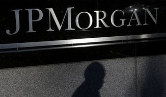The shadows of a pedestrian is cast under a sign in front of JPMorgan Chase & Co. headquarters in New York on Nov. 19, 2013. (Associated Press)