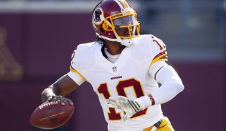 Washington Redskins quarterback Robert Griffin III (10) throws the ball against the Minnesota Vikings during an NFL football game, Sunday, Nov. 2, 2014, in Minneapolis. (Jeff Haynes/AP Images for Panini)