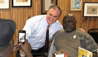 Sen. Mark Pryor, D-Ark. center, poses for a picture with Little Rock resident Christopher King, right, while Howard Nash of Little Rock, steadies his camera at Sim's Barbecue restaurant in Little Rock, Ark., Tuesday, Nov. 4, 2014, on election day. (AP Photo/David Quinn)