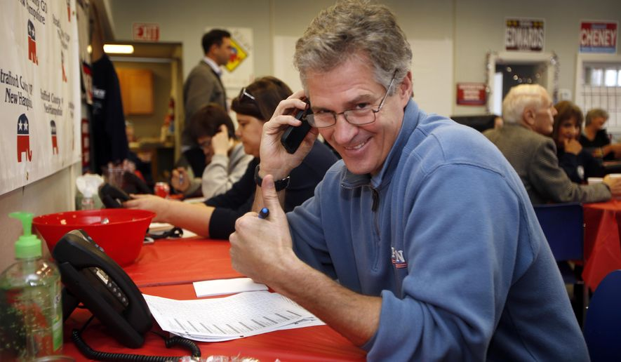 New Hampshire Republican Senate candidate Scott Brown gives a thumbs up as he calls voters on election day from the Republican field office, Tuesday, Nov. 4, 2014, in Dover, N.H. Brown is trying to unseat incumbent U.S. Sen. Jeanne Shaheen.  (AP Photo/Jim Cole)