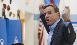 Sen. Mark Warner, D-Va., celebrates after registering his vote at Lyles-Crouch Traditional Academy on Tuesday, Nov. 4, 2014 in Alexandria, Va. Incumbent Democrat Sen. Mark Warner looks to retain his seat in the U.S. Senate for a second term. He faces Republican Ed Gillespie. (AP Photo/Kevin Wolf)