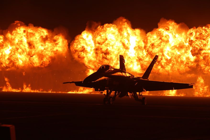 Flames explode behind the U.S. Navy Blue Angels'  F/A-18 Hornets during the night portion of the 2014 Miramar Air Show aboard Marine Corps Air Station Miramar, Calif., Oct. 4. The wall of fire is the last event of the night air show.