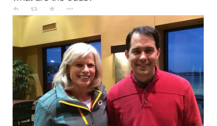 In this frame grab provided by Mary Burke's campaign Republican Wisconsin Gov. Scott Walker and Democratic challenger Mary Burke pose for a photo tweeted Tuesday, Nov. 3, 2014 by Burke's campaign after the two ran into each other at the airport in Green Bay, Wis.  The two are locked in a close race for governor and have been rushing around the state in last-minute, get-out-the vote efforts. (AP Photo/Mary Burke campaign)