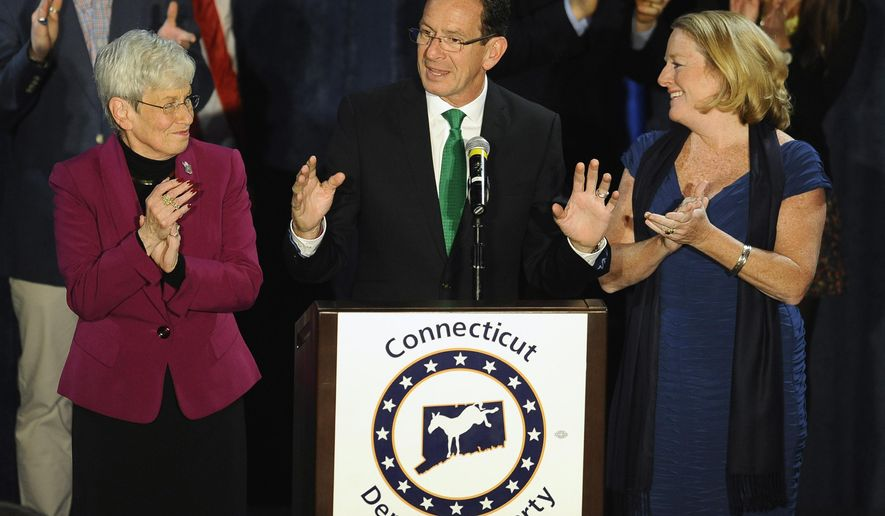 Incumbent Democratic Gov. Dannel P. Malloy, center, speaks to supporters as Lt. Gov. Nancy Wyman, left, and his wife Cathy Malloy, right, listen, at his party's rally, Wednesday, Nov. 5, 2014, in Hartford, Conn. (AP Photo/Jessica Hill)