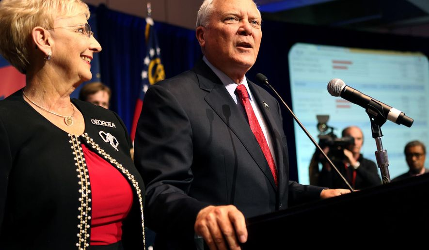 Georgia Governor Nathan Deal with his wife Sandra greets supporters after winning re-election against Democratic opponent Jason Carter at the College Football Hall of Fame in Atlanta, Tuesday, Nov. 4, 2014. (AP Photo/Akili-Casundria Ramsess)