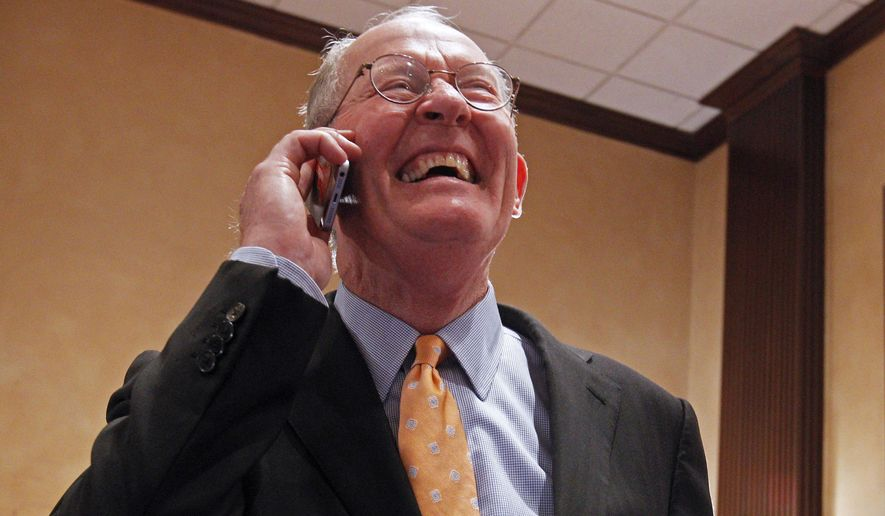 U.S. Sen. Lamar Alexander, R-Tenn. smiles as he talks on the phone after retaining his seat in the Senate, Tuesday, Nov. 4, 2014, in Knoxville, Tenn. (AP Photo/Wade Payne)