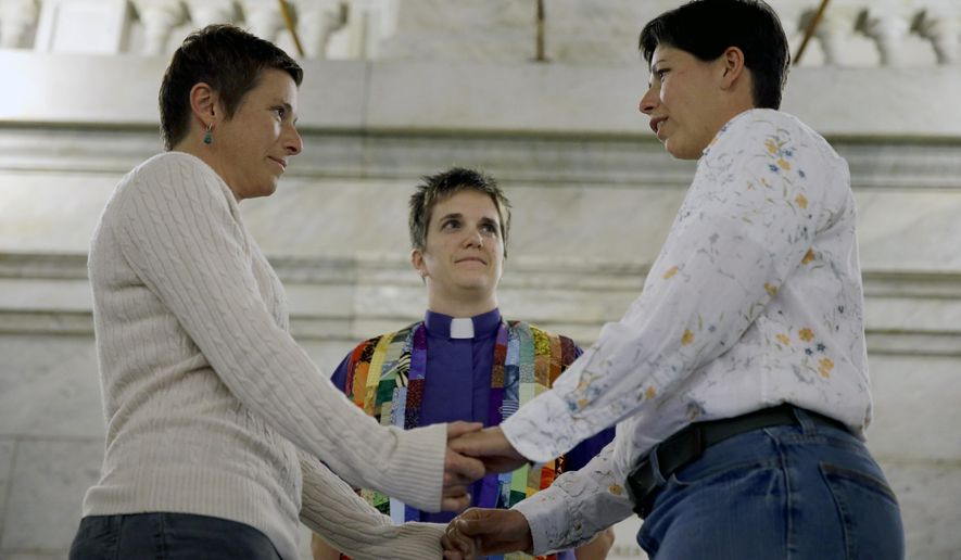 April Dawn Breeden, left, and her long-time partner Crystal Peairs, right, are married by Rev. Katie Hotze-Wilton, Wednesday, Nov. 5, 2014, at City Hall in St. Louis. St. Louis Circuit Judge Rex Burlison overturned Missouri's ban on gay marriage on Wednesday saying the law is unconstitutional. (AP Photo/Jeff Roberson)