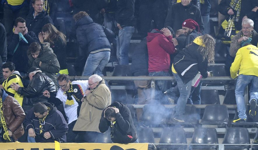 Dortmund fans take cover as fireworks explode during the Champions League group D soccer match between Borussia Dortmund and Galatasaray Istanbul in Dortmund, Germany, Tuesday, Nov.4,, 2014. (AP Photo/Martin Meissner)