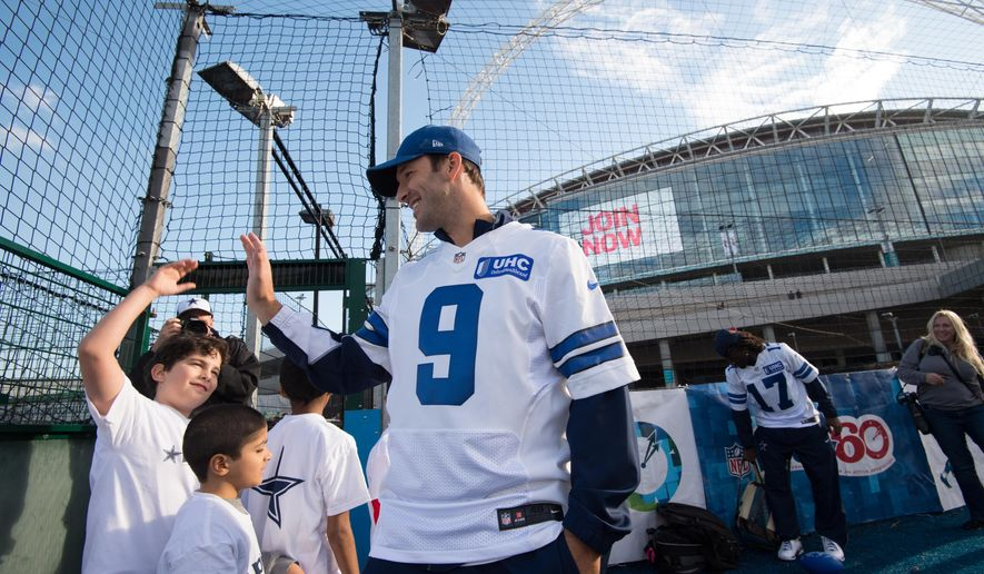 Dallas Cowboys quarterback Tony Romo meets local children during a community day event outside Wembley Stadium in London, England, Tuesday Nov. 4, 2014. The Dallas Cowboys will play the Jacksonville Jaguars in an NFL football game at Wembley Stadium on Sunday Nov. 9 (AP Photo/Tim Ireland)