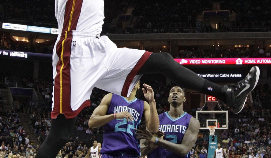 Miami Heat's Josh McRoberts, front, dunks in front of Charlotte Hornets' Brian Roberts, back left, and Marvin Williams during the first half of an NBA basketball game in Charlotte, N.C., Wednesday, Nov. 5, 2014. (AP Photo/Chuck Burton)