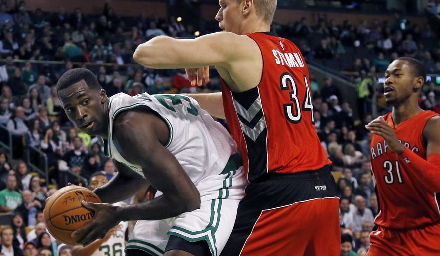 Boston Celtics forward Brandon Bass looks to pass the ball against the defense of Toronto Raptors center Greg Stiemsma (34) and forward Terrence Ross (31) during the first quarter of an NBA basketball game in Boston, Wednesday, Nov. 5, 2014. (AP Photo/Elise Amendola)