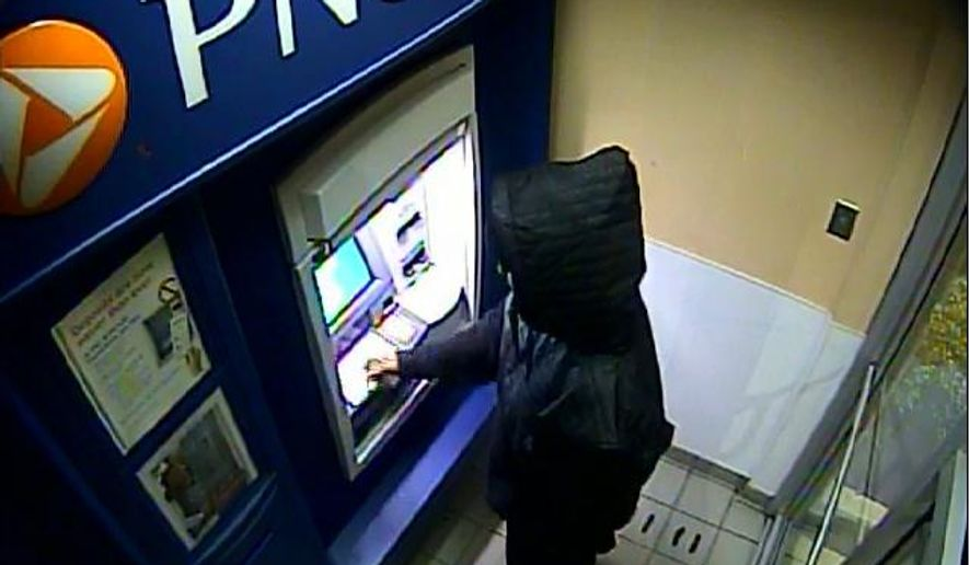 This image taken from a surveillance video early Monday morning, Nov. 3, 2014, and released by the Philadelphia Police Department, shows an unknown man at an ATM machine in Aberdeen, Md., using Carlesha Freeland-Gaither's bank card. The transaction occurred less than nine hours after the reported abduction Sunday night, Nov. 2, of the Philadelphia woman. (AP Photo/Philadelphia Police Department)