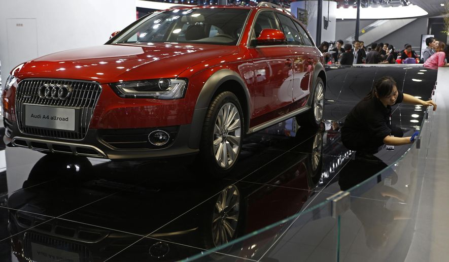 FILE - In this Nov. 22, 2012 photo, a worker cleans the booth featuring the Audi A4 allroad at the Guangzhou 2012 Auto Show in China's southern city of Guangzhou. Audi on Wednesday, Nov. 5, 2014 announced it is recalling nearly 102,000 A4 and S4 cars from the 2013 through 2015 model years, plus the 2013 through 2015 Audi Allroad, because the front air bags may not inflate in a crash. (AP Photo/Vincent Yu, File)