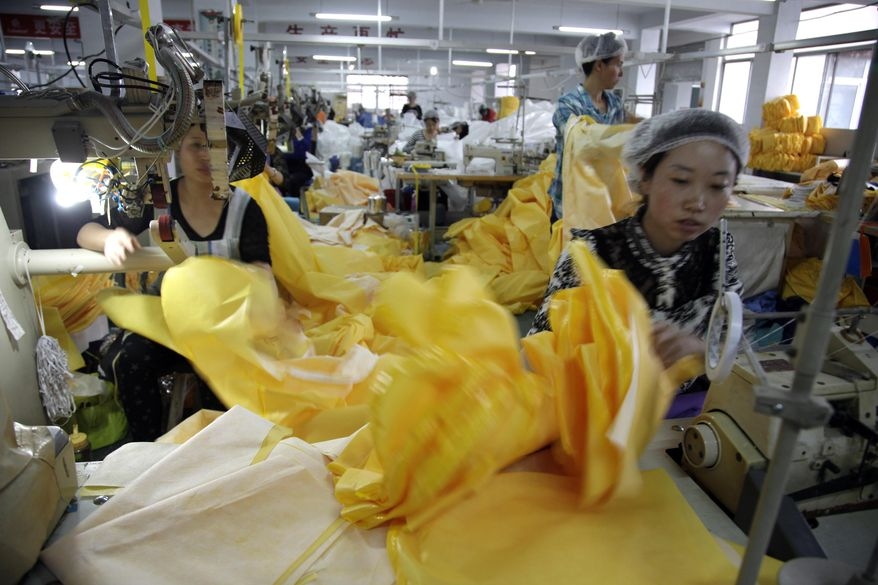 In this photo taken Thursday, Oct. 30, 2014, Chinese workers manufacture protection suits that meet the standards for use by healthcare workers treating Ebola patients at a factory of U.S. based Lakeland Industries in Anqiu city in eastern China's Shandong Province. Far from the Ebola hot zone, the sewing and gluing machines at a factory in China have been whirring more than usual to produce crucial yellow suits that protect the front-line medics more than 11,000 kilometers (7,000 miles) away in West Africa. (AP Photo/Wayne Zhang)