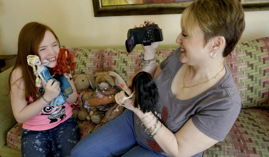 """In this Monday, Oct. 27, 2014 photo, Gracie Hunter, left, and her Mom, Melissa make a video for a doll review while on vacation in Kissimmee, Fla. The mother-daughter duo, stars of the """"Mommy and Gracie"""" YouTube show, review dolls for kids. (AP Photo/John Raoux)"""