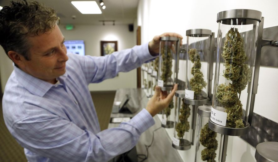 Shane Mckee, co-founder of Shango Premium Cannabis dispensary, pulls a  medical marijuana sample from their display of cannabis flowers in Portland, Ore., Wednesday, Nov. 5, 2014. Oregon voters have made their state the third to legalize recreational pot, but it will be more than a year before the first shops open.  But dispensaries that already sell medical marijuana are expected to start taking steps to get their applications in to sell recreational weed as well.  (AP Photo/Don Ryan)