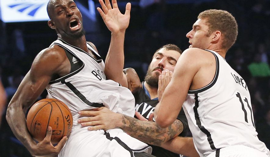 Brooklyn Nets center Kevin Garnett (2) grimaces as he gets tangled up while stealing the ball from Minnesota Timberwolves center Nikola Pekovic, as Nets center Brook Lopez (11) helps defend during the first half of an NBA basketball game Wednesday, Nov. 5, 2014, in New York. (AP Photo/Kathy Willens)