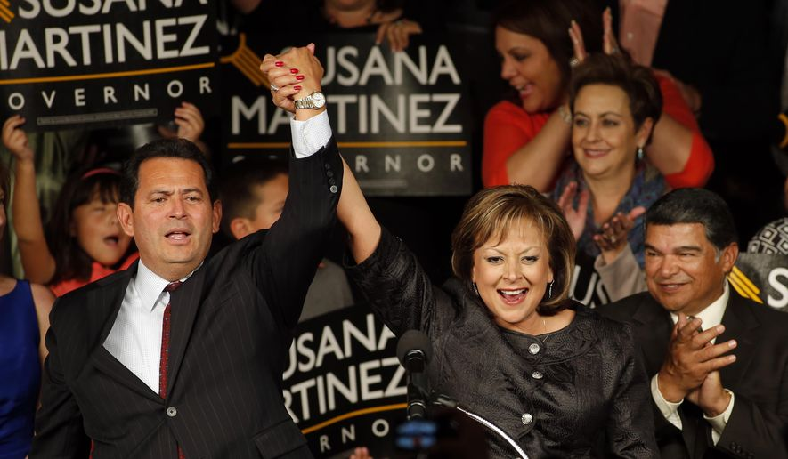 New Mexico Gov. Susana Martinez, center, and Lt. Gov. John Sanchez, left, celebrate with supporters during the victory party on election night in Albuquerque, N.M., Tuesday, Nov. 4, 2014. Martinez was re-elected beating Democratic challenger Gary King. (AP Photo/Andres Leighton)