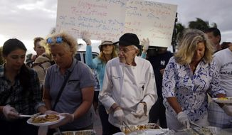 Homeless advocate Arnold Abbott, 90, director of the nonprofit group Love Thy Neighbor Inc., center, serves food to the homeless with the help of volunteers from a public parking lot next to the beach, Wednesday, Nov. 5, 2014, in Fort Lauderdale, Fla. Abbott was later issued a summons to appear in court for violating an ordinance that limits where charitable groups can feed the homeless on public property.  Abbott was also recently arrested along with two pastors for feeding the homeless in a Fort Lauderdale park. (AP Photo/Lynne Sladky)