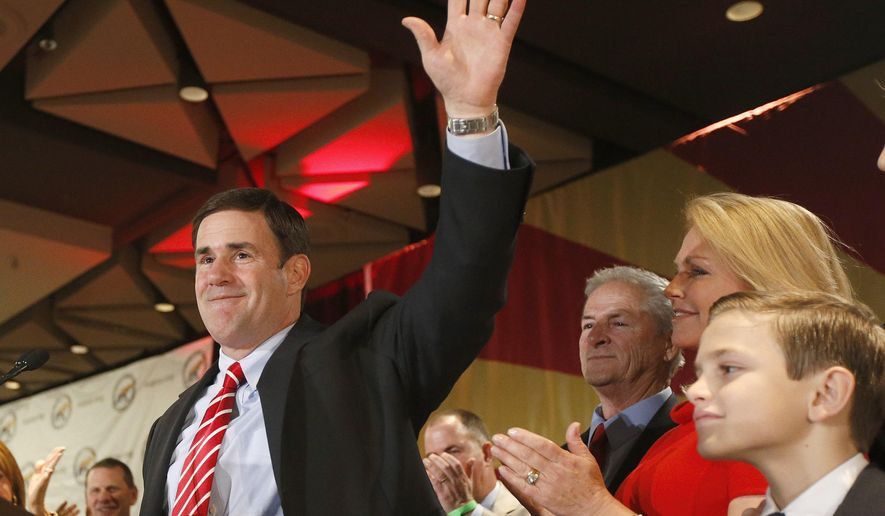Before giving his acceptance speech, Republican candidate for governor Doug Ducey, waves to supporters as his wife Angela Ducey, second from right, and son Sam Ducey, right, look on at election night festivities Tuesday, Nov. 4, 2014, in Phoenix.