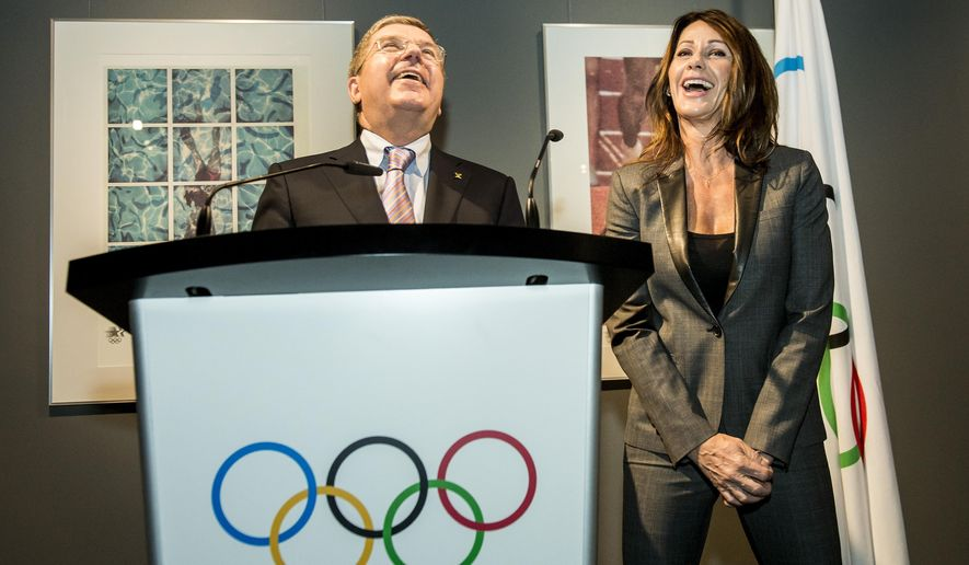 Former Olympic gymnast Nadia Comaneci from Romania, right, next to International Olympic Committee (IOC) president German Thomas Bach, left, attend a news conference at the Olympic Museum, in Lausanne, Switzerland, Tuesday, Nov. 4, 2014. Comaneci made a donation of her bib worn during the 1976 Olympic Games in Montreal. Winner of three Olympic gold medals at the 1976 Summer Olympics in Montreal, Nadia Comaneci, was the first female gymnast to be awarded a perfect score of 10 in an Olympic gymnastic event. (AP Photo/Keystone,Jean-Christophe Bott)