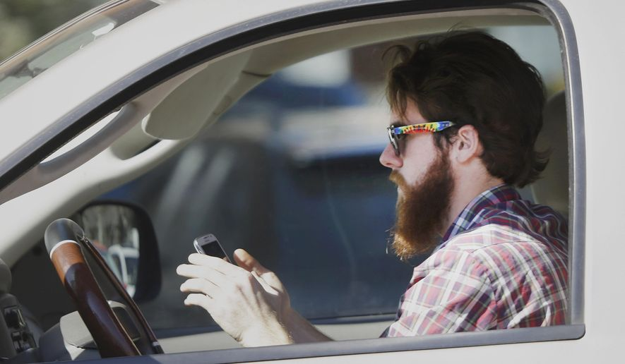 In this Feb. 26, 2013 file photo, a man uses his cell phone as he drives through traffic in Dallas.  (AP Photo/LM Otero) **FILE**