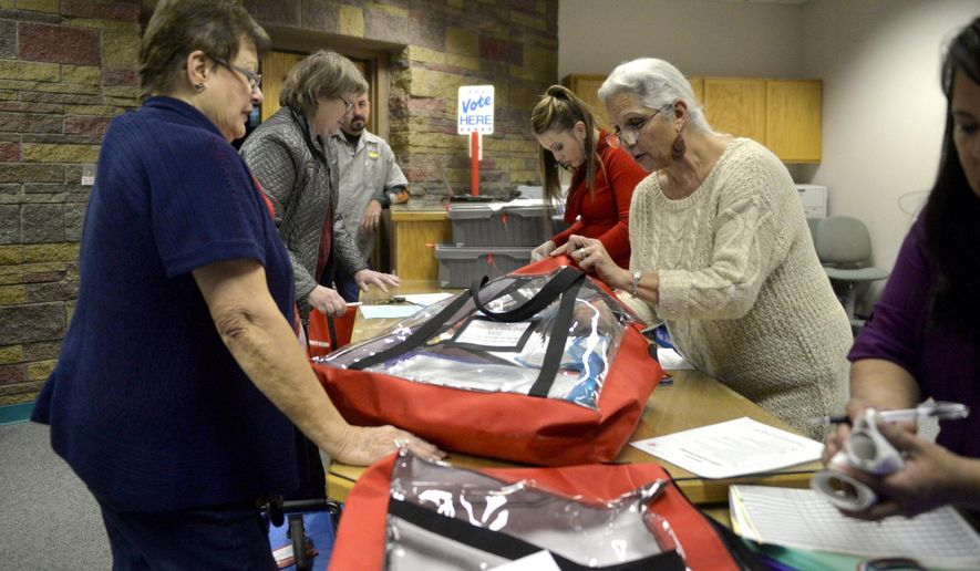 Workers at the San Juan County Clerk's Office in Aztec, N.M., go through election bags with presiding judges on Tuesday, Nov. 4, 2014, after the polls closed in Aztec, N.M.  (AP Photo/The Daily Times, Alexa Rogals)