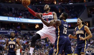 Washington Wizards guard John Wall (2) drives to the basket past Indiana Pacers guard Donald Sloan (15) during the first half of an NBA basketball game, Wednesday, Nov. 5, 2014, in Washington. (AP Photo/Alex Brandon)