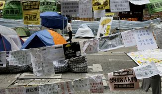 A pro-democracy protester walks at a main road in the occupied area of the Causeway Bay district in Hong Kong Wednesday, Nov. 5, 2014. (AP Photo/Vincent Yu)