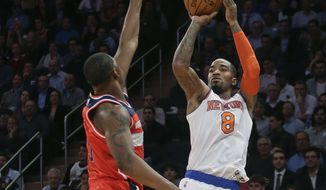 New York Knicks' J.R. Smith (8) shoots over Washington Wizards' Kevin Seraphin (13) during the second half of an NBA basketball game Tuesday, Nov. 4, 2014, in New York. The Wizards won the game 98-83. (AP Photo/Frank Franklin II)