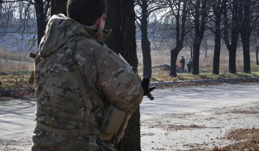 A pro-Russian rebel stands guard as women walk along a street not far from the front line near Donetsk airport in the city of Donetsk, eastern Ukraine Sunday, Nov. 2, 2014. The pro-Russian rebels are holding the elections that were dismissed by Ukraine and the West as illegitimate. (AP Photo/Dmitry Lovetsky)
