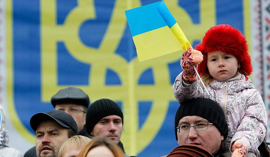 A child holds a Ukrainian flag during a rally against voting in the Donetsk and Luhansk regions in Kiev, Ukraine Sunday, Nov. 2, 2014. Some of participants are refugees from Donetsk and Luhansk regions. (AP Photo/Sergei Chuzavkov)