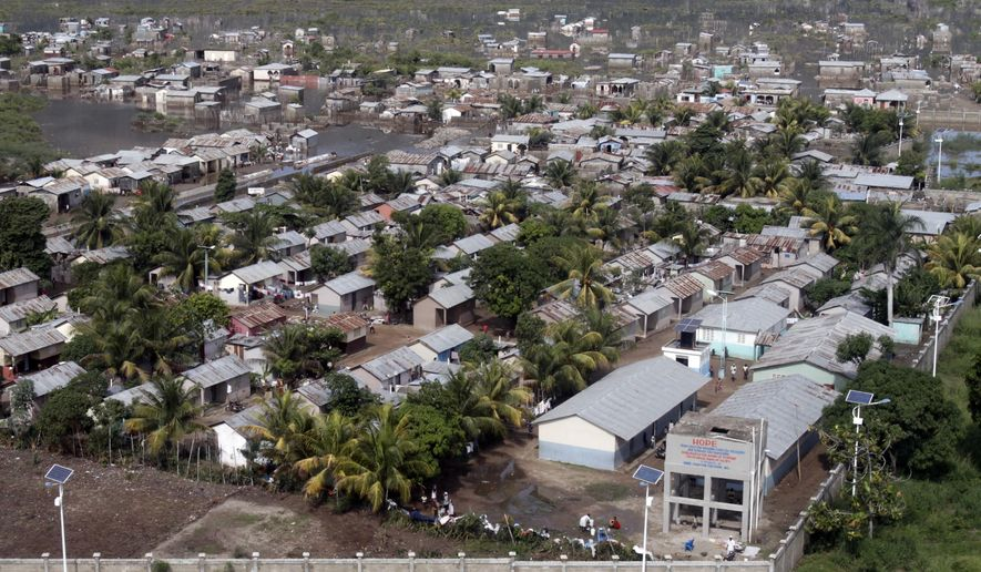 Some building stand in floodwater after heavy rain in Cap-Haitien, Haiti, Thursday, Nov. 6, 2014. Haiti's Department of Civil Protection said at least 6,000 homes were flooded in Cap-Haitien and several nearby communities. Also, at least five people were killed and one is missing. (AP Photo/Luxama Pierre Richard)