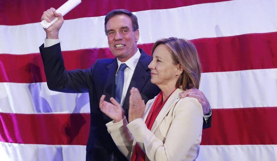 Sen. Mark Warner, D-Va., waves to the crowd with his wife, Lisa Collis during an election party in Arlington, Va., Wednesday, Nov. 5, 2014. Warner is locked in a tight race with Republican Ed Gillespie. (AP Photo/Steve Helber)