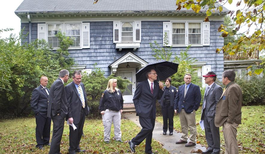 In this Oct. 10, 2014 photo, Topeka officials, including Mayor Larry Wolgast, holding umbrella, toured vacant homes in Topeka, Kan., with several members of a joint Kansas Legislature committee to illustrate the problem of vacant homes in Topeka. RealtyTrac says Kansas has the third-highest rate of vacancies, with 31 percent of homes in the foreclosure process abandoned. (AP Photo/The Topeka Capital-Journal, Thad Allton)