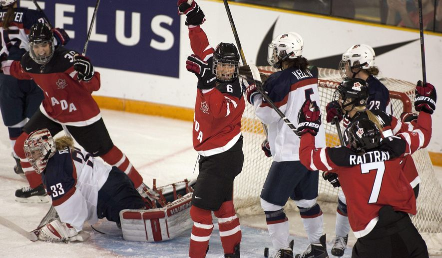 Team Canada Rebecca Johnston, center, celebrates a goal past Team USA goalie Alex Rigsby (33) during the first period of a women's Four Nations Cup hockey game Wednesday, Nov. 5, 2014, in Kamloops, British Columbia. Team Canada Players Halli Krzyzaniak, Left, And Jamie Lee Rattray Join In On The Celebration. (AP Photo/The Canadian Press, Jeff Bassett)