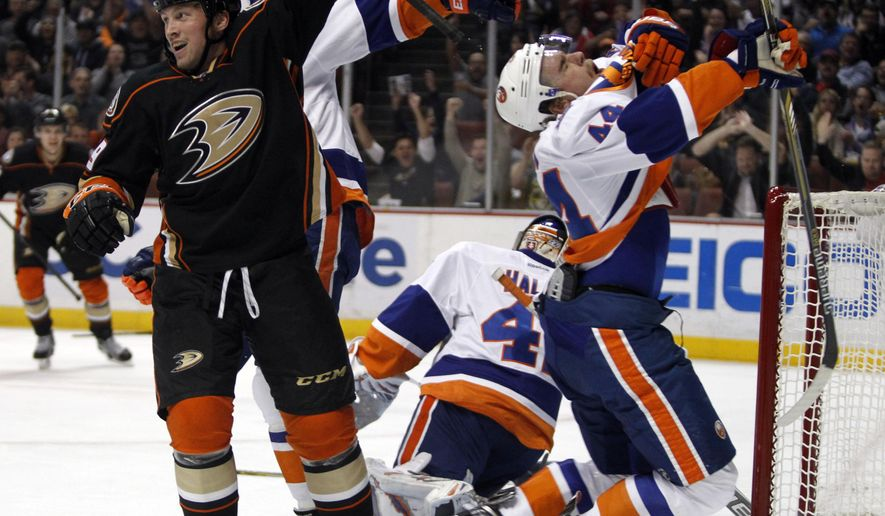Anaheim Ducks left wing Matt Beleskey, left, reacts after scoring, while New York Islanders defenseman Calvin de Haan (44) reacts after a stick to the face during the second period of an NHL hockey game, in Anaheim, Calif., Wednesday, Nov. 5, 2014. (AP Photo/Alex Gallardo)