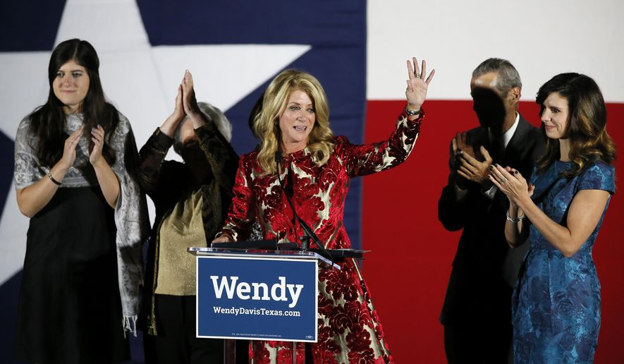 File - In this Nov. 4, 2014 file photo, Texas Democratic gubernatorial candidate Wendy Davis waves to supporters after making her concession speech, in Fort Worth, Texas. Davis' family, from left, daughter Dru, mother Ginger Russell, brother Joey Russell and daughter Amber, right, watch during the speech. Exit polls show that Davis did no better with women than her Democratic predecessor in 2010 despite being one of highest profile female candidates in the U.S. and making issues like equal pay and reproductive rights cornerstones of her campaign. (AP Photo/Tony Gutierrez, File)