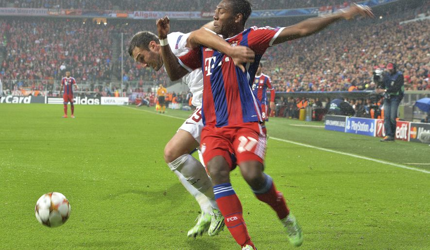 Roma's Vasilis Torosidis, left, and Bayern's David Alaba challenge for the ball during the Champions League group E soccer match between Bayern Munich and Roma in Munich, Germany, on Wednesday, Nov. 05, 2014. (AP Photo/Kerstin Joensson)