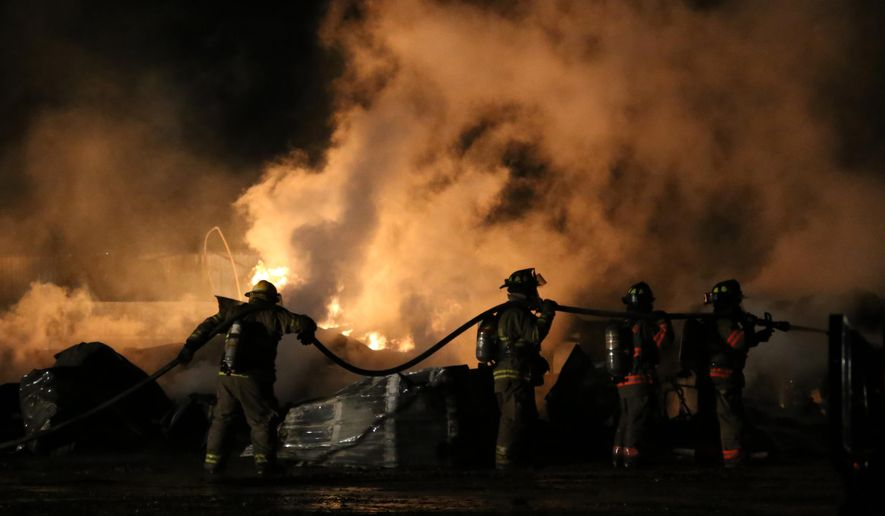 In this photo taken Wednesday night, Nov. 5, 2014, firefighters follow an excavator as they battle a blaze at David Allen Racing Motorsports in Fremont, Mich. No injuries are reported. The cause is under investigation Thursday. (AP Photo/The Muskegon Chronicle, Andraya Croft) ALL LOCAL TELEVISION OUT; LOCAL TELEVISION INTERNET OUT