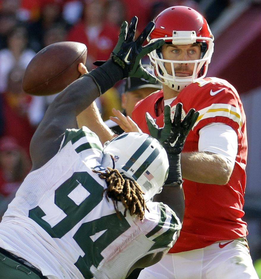 Kansas City Chiefs quarterback Alex Smith (11) throws under pressure from New York Jets nose tackle Damon Harrison (94) in the second half of an NFL football game in Kansas City, Mo., Sunday, Nov. 2, 2014. (AP Photo/Charlie Riedel)