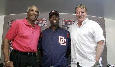 Newly acquired Washington Nationals player Alfonso Soriano, center, stands with team manager Frank Robinson, left, and Jim Bowden, vice president and general manager of the Nationals, following a news conference, Thursday, Feb. 23, 2006, at the team's Major League Baseball spring training facility in Viera, Fla. (AP Photo/Haraz N. Ghanbari)
