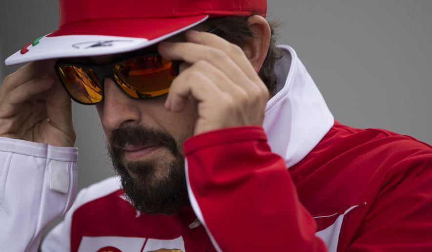 Ferrari driver Fernando Alonso of Spain puts on his sunglasses as he walks on the paddock of the Interlagos circuit in Sao Paulo, Brazil, Thursday, Nov. 6, 2014.  Formula One teams are in Sao Paulo to compete in the 2014 Brazilian Grand Prix, Sunday. (AP Photo/Felipe Dana)