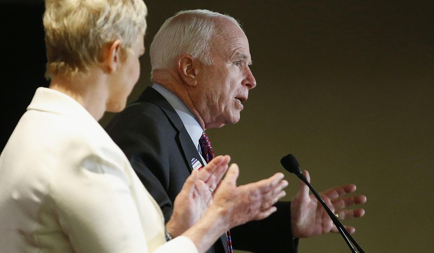 Arizona Republican Sen. John McCain, right, speaks to the crowd as wife Cindy McCain applauds her husband at election night festivities Tuesday, Nov. 4, 2014, in Phoenix. (AP Photos/Ross D. Franklin)
