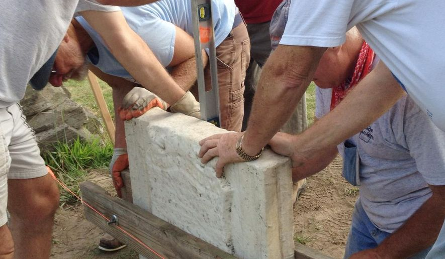 In this Monday, Aug. 25, 2014 photo, volunteers from the Brighton Area Historical Society and a local chapter of the Sons of the Union Veterans of the Civil War lift the Lt. Col. John Gilluly headstone into place in Brighton, Mich. The Brighton Area Historical Society recently rebuilt the broken 500-pound headstone for the local Civil War soldier. A rededication will be held Saturday for the headstone, The Livingston County Daily Press & Argus of Howell reported. (AP Photo/Livingston County Daily Press & Argus, Jim Totten)