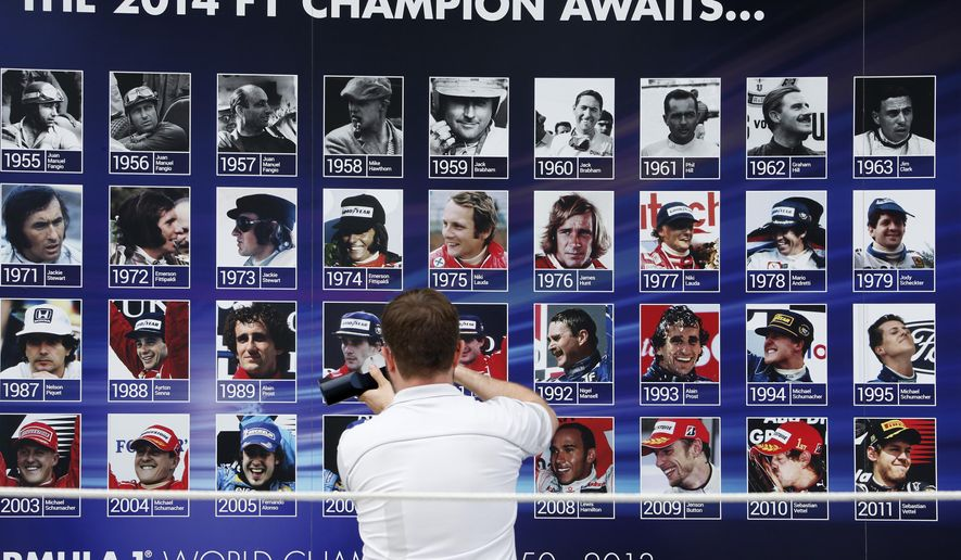 A staff support members prepares the winner's podium for this weekend's 2014 Brazilian Grand Prix, decorating a backdrop with photos of previous champion drivers, at the Interlagos circuit in Sao Paulo, Brazil, Thursday, Nov. 6, 2014. (AP Photo/Andre Penner)