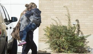 A Sandy family returns home with their daughter after the girl's father rescued her from a man who tried to kidnap her on Friday, Nov. 7, 2014, in Sandy, Utah. The Utah dad foiled an attempt to kidnap his young daughter from her bed early Friday after confronting a man carrying her across the lawn. (AP Photo/The Salt Lake Tribune, Rick Egan)  DESERET NEWS OUT; LOCAL TELEVISION OUT; MAGS OUT