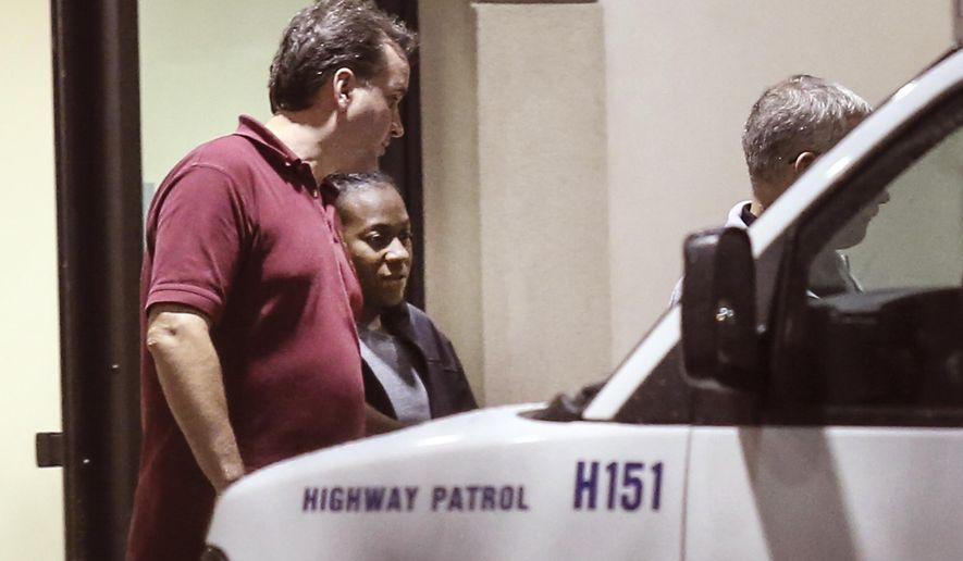 Carlesha Freeland-Gaither, second from left, is escorted from Howard County General Hospital in Columbia, Md., early Thursday morning, Nov. 6, 2014, by Philadelphia Detectives James Sloan, left, and John Geliebter, right, partially obscured. (AP Photo/Philadelphia Daily News, Steven M. Falk)